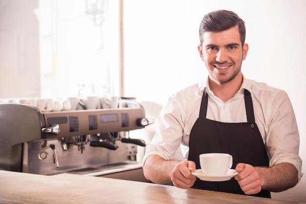 Barista prepara capuchino en su cafetería.