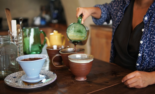 Barista preparando café con cafetera y tetera de goteo. goteo de café molido con filtro