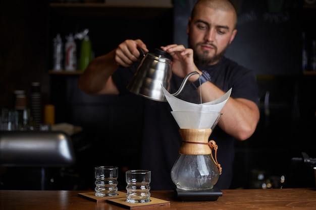 Barista preparando café con chemex pour over coffee maker