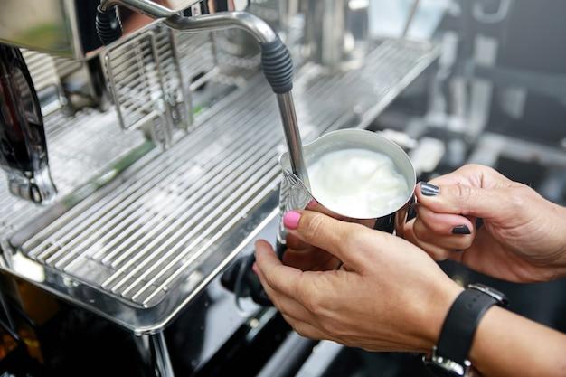 Barista está preparando café. leche humeante y espumosa para capuchino o café con leche.