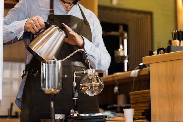 Barista de primer plano vierte agua hirviendo caliente de kattle en dispositivo de sifón de vidrio para preparar café en la cafetería