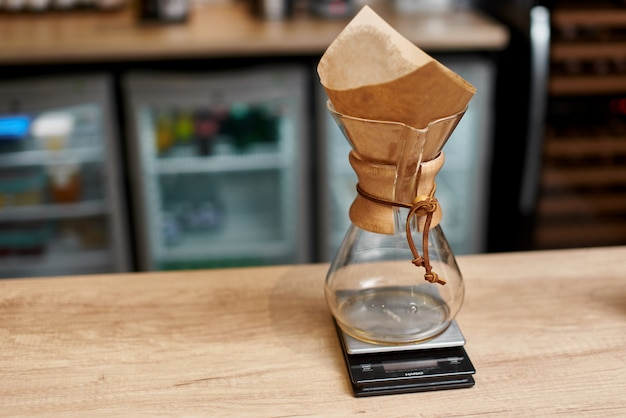 Barista profesional preparando café con chemex vierta sobre la cafetera y la tetera de goteo. formas alternativas de preparar café. concepto de cafetería