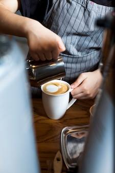 Barista profesional vertiendo espuma con leche en un café en la cafetería