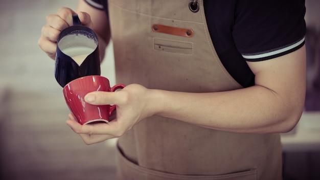 Barista profesional vertiendo leche fluida para hacer café con leche en una taza roja de café caliente, tono retro