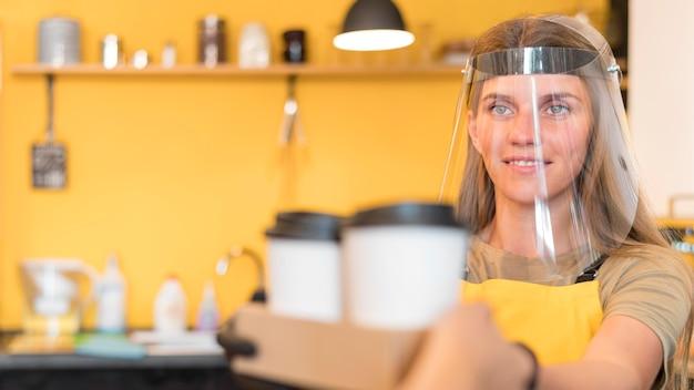 Barista con protección facial cuando sirve
