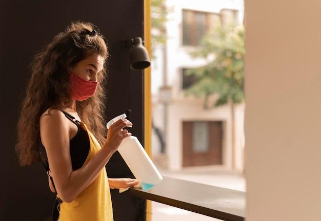 Barista rizado con una mascarilla mientras limpia en la cafetería.