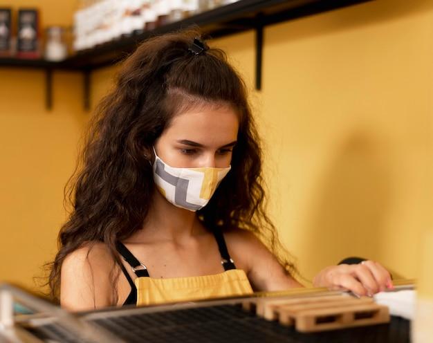 Barista rizado con una mascarilla mientras prepara café