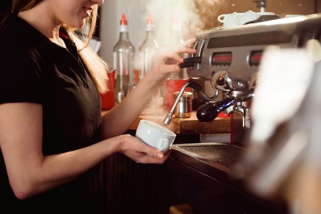 Barista de sexo femenino que hace el café en contador de la cafetería. mujer barista trabajando en cafe