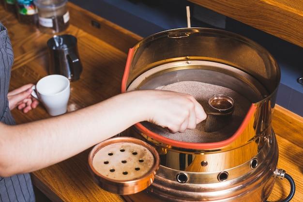 Barista de sexo femenino que prepara el café turco en cezve en la arena en la barra de café