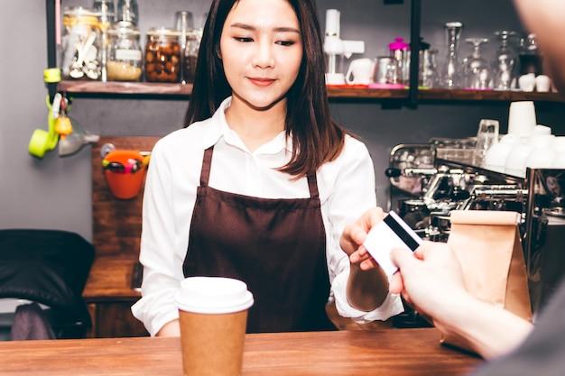 Barista de sexo femenino que toma una tarjeta de crédito del cliente en cafetería