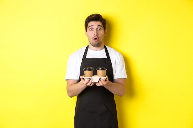 Barista sirviendo café, mirando sorprendido a la cámara, vestido con delantal negro, de pie contra un fondo amarillo.