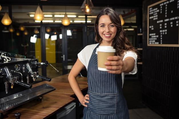 Barista sonriente que sostiene la taza disponible