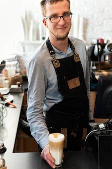 Barista sonriente de tiro medio sosteniendo un vaso