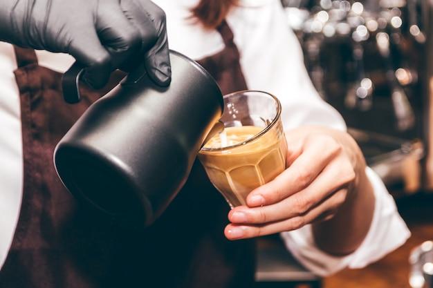 Barista sosteniendo leche para hacer café con leche arte en cafetería