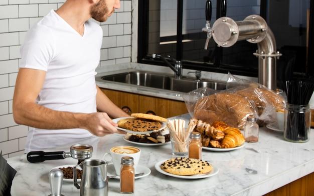 Barista sosteniendo en la mano un plato de galletas