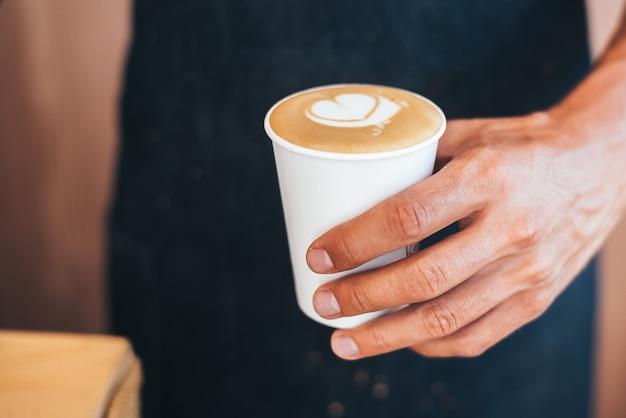 El barista sostiene el café terminado en su mano en un vaso de papel con un patrón de corazón hecho con crema.