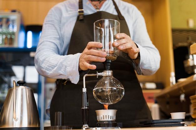 Barista sostiene el dispositivo de sifón en las manos antes de preparar el café en la cafetería