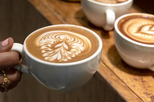 Barista sostiene taza de café latte art.