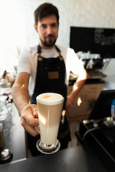 Barista de tiro medio sosteniendo la taza de café