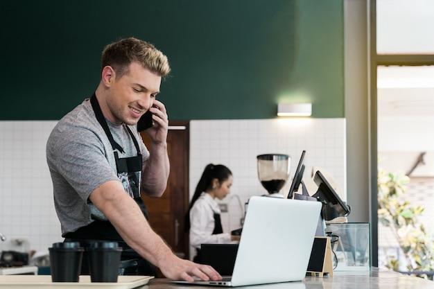 Barista usa una computadora portátil para tomar el pedido del cliente en el mostrador de café