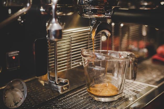 Barista usando máquina de café en la cafetería.