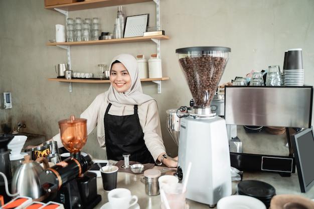 Barista velado sonriendo cuando sostiene una taza de café