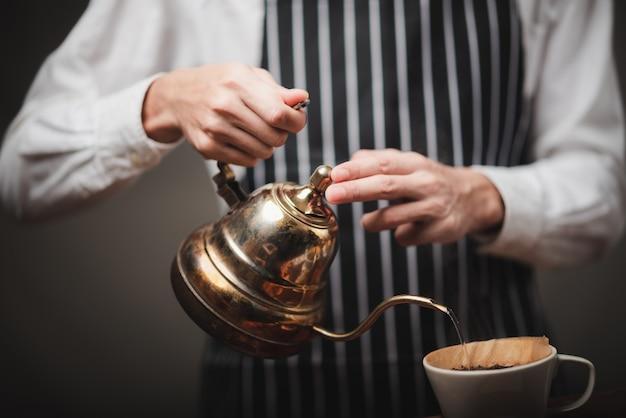 Barista vertiendo agua caliente de la tetera sobre el café en polvo para extraer el café recién hecho en la cafetería.