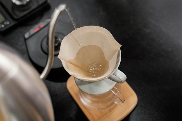 Barista vertiendo agua hirviendo en el filtro de café