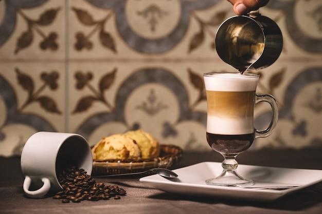Barista vertiendo el almíbar en un café con leche en capas