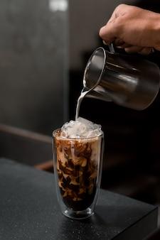 Barista vertiendo café en vaso
