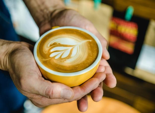 Barista vertiendo leche en una taza de café.
