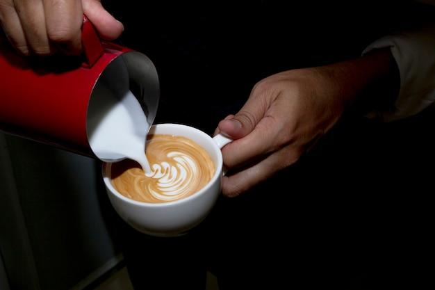 Barista vertiendo leche en una taza de café para hacer arte con leche.