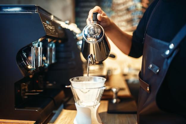 Barista vierte agua caliente en el vaso con café