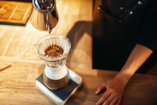 Barista vierte agua caliente en el vaso, latte
