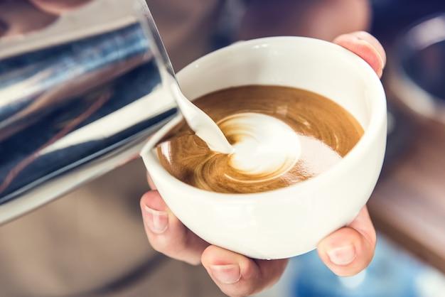Barista vierte leche al vapor en una taza de café haciendo arte con leche