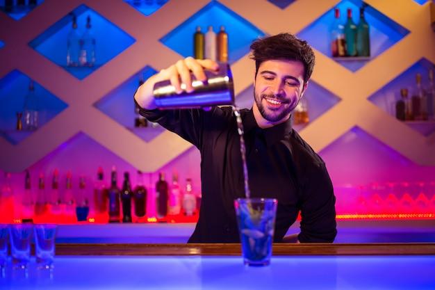 Barkeeper vertiendo cóctel en vaso en mostrador