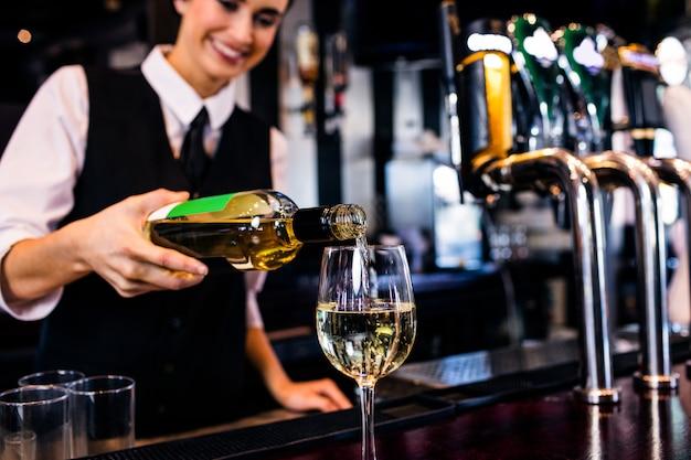 Barmaid sirviendo una copa de vino en un bar