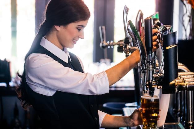 Barmaid sirviendo una pinta en un bar