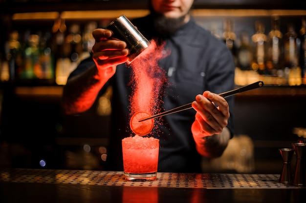 Barman agregando especias en polvo en una copa de cóctel con una rodaja de limón