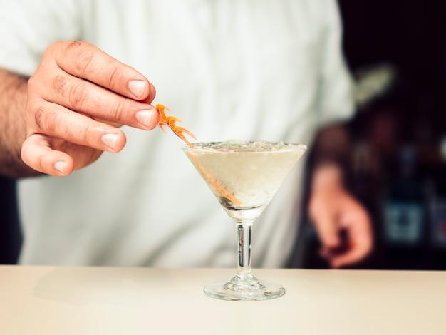 Barman añadiendo decoración al cóctel.