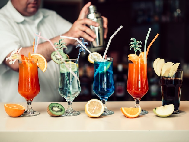 Barman anónimo mezclando bebidas en coctelera y sirviendo vasos brillantes