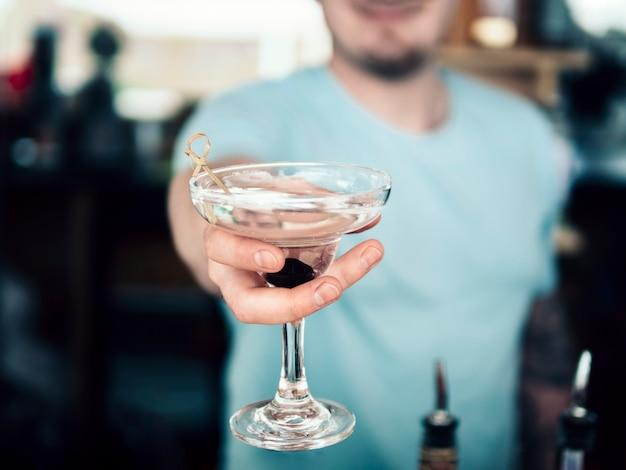 Barman anónimo que sirve una copa de bebida decorada