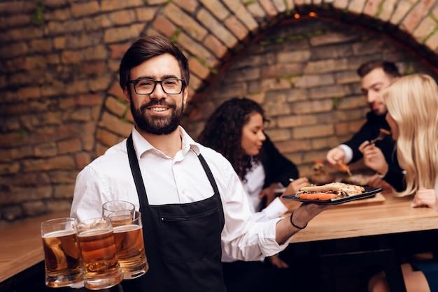 Barman barbudo trajo cerveza y bocadillos a los clientes.