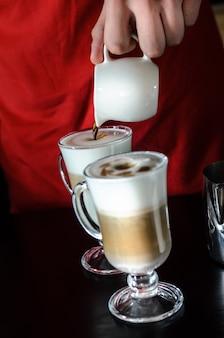 El barman barista detrás del mostrador hace café con leche, sirve y evita