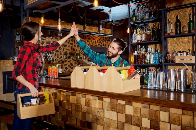 Barman y camarero trabajan junto con el equipo en el bar restau