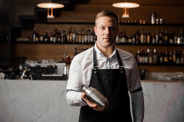 Barman en camisa blanca y delantal sosteniendo una coctelera