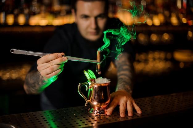 Barman decorando cóctel fresco en copa de oro con palitos de canela ardiendo