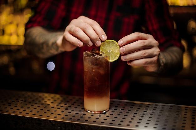 Barman decorar copa de cóctel con bebida alcohólica fresca con una rodaja de limón amarillo fresco