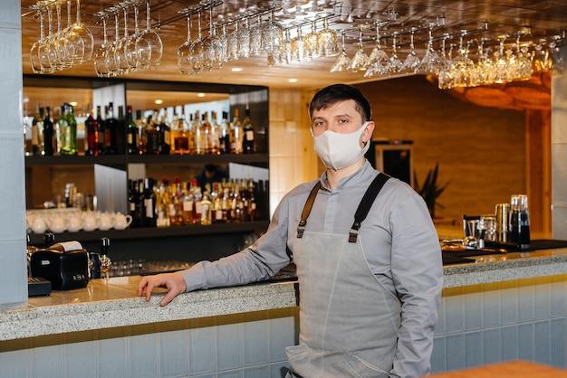 Un barman elegante con máscara y uniforme durante una pandemia. el trabajo de los restaurantes y cafés durante la pandemia.