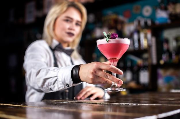 El barman experimentado sorprende con su barra de habilidades a los visitantes mientras está de pie cerca de la barra del bar en la discoteca